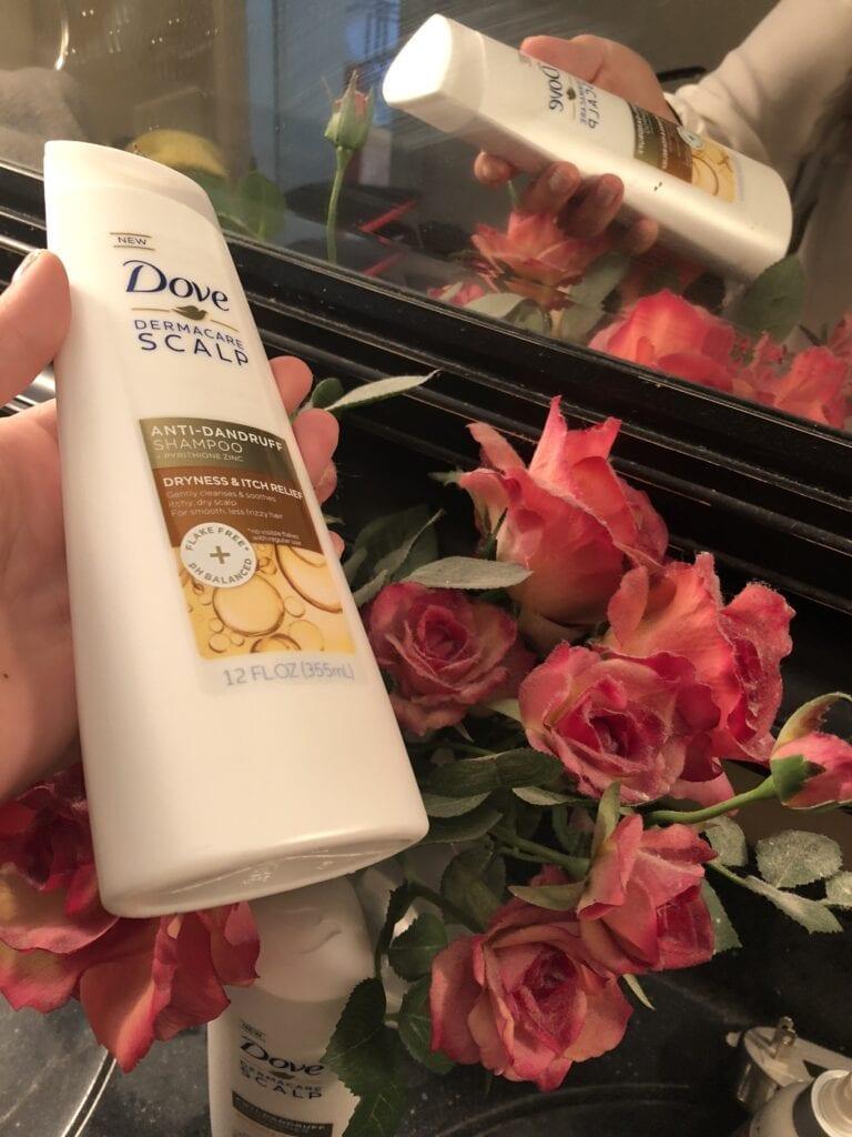Sarah holding Dove Dermacare Anti-Dandruff shampoo bottle