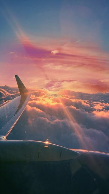 An airplane traveling through a sunset and clouds.