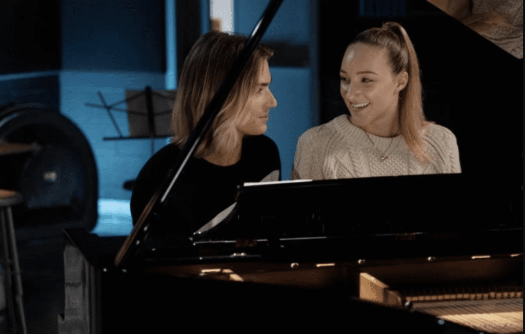 Boy and girl sit at piano in Netflix Original rom-com Tall Girl