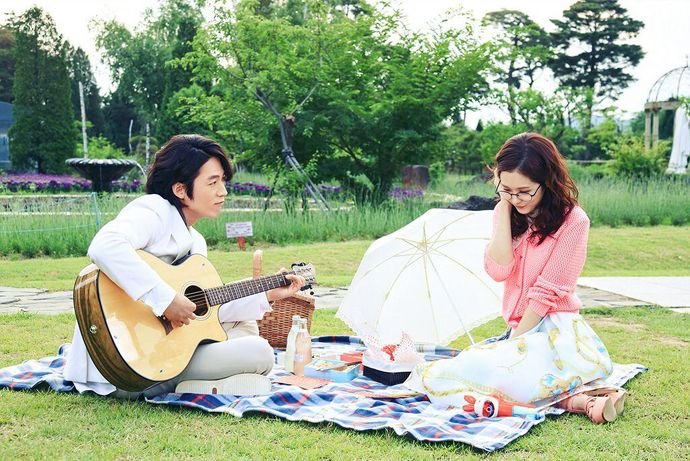 Fated to Love You scene: A person holding a guitar in a park