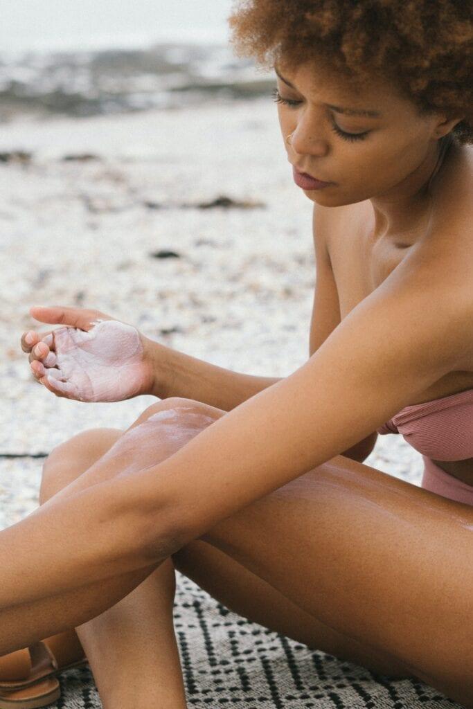 Woman in pink bikini applying sunscreen