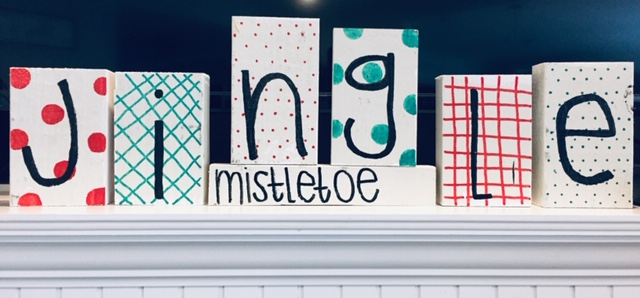 Blocks of wood decorated to spell out the word JINGLE with small block underneath reading MISTLETOE