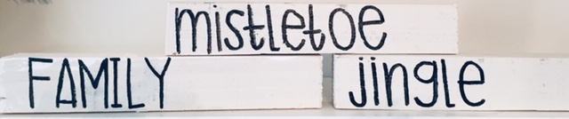 small white blocks with various words written on them: mistletoe, family, jingle
