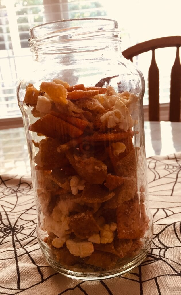mason jar filled with salty snack mix sitting on kitchen table