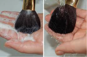 Soapy makeup brush being swirled on the palm of a hand and being rinsed.