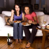 Two women eating junk food and drinking wine