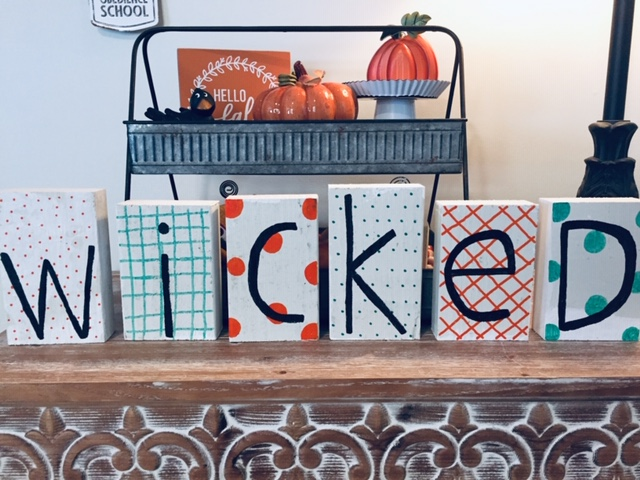 Final product: letter blocks with green and orange accents spelling out WICKED in black print