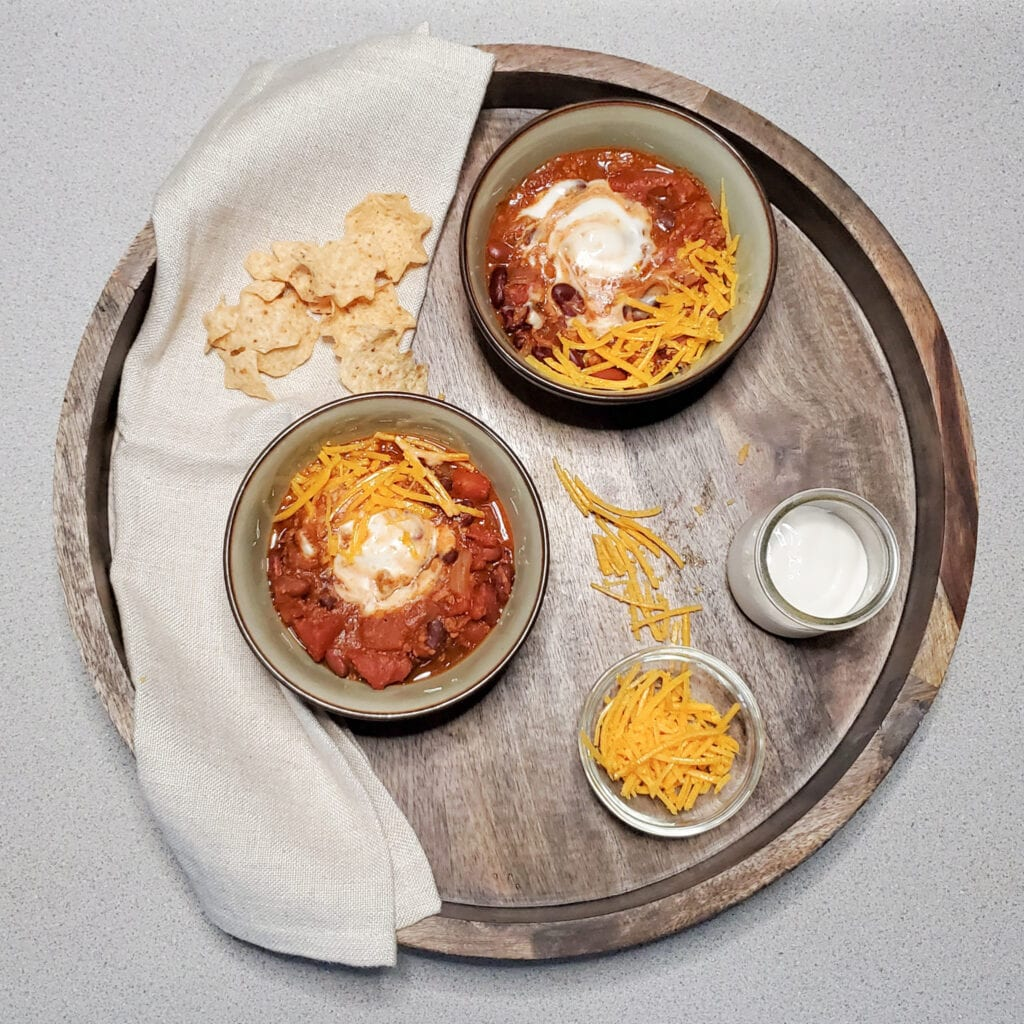 A round serving tray with two bowls of vegan chili, and a side of vegan cheese and vegan sour cream. This is a decorative image.